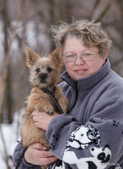 Фото рыжего щенка питомника Еливс у владельца на руках вовремя прогулки зимой